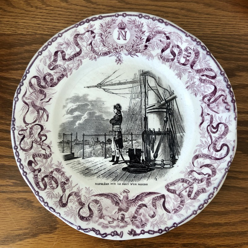 "French Napoleon Commerative Assiettes Parlantes Plate. c.1840s ""Napoleon Sur Le Pont D'un Navire""<br /> Assiettes Parlantes, or talking plates, are French transferware plates with sayings on them. The most collectible illustrate the life of a French hero such as the plates depicting Napoleon. Really unusual to find in purple. 8""."