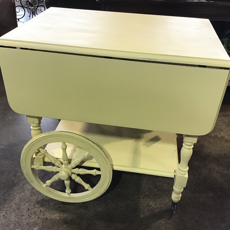 "This vintage tea cart has been updated in-house with Country Chic's Bees Knees (creamy yellow) paint, lightly distressed and clear waxed for protection. This lovely cart is on wheels and has drop-down sides that can be raised to serve during a gathering. Beautiful color that would add a ""pop"" to any space!<br /> Dimensions closed are 20"" x 28"" x 28""<br /> Dimensions open are 39"" x 28"" x 28"""