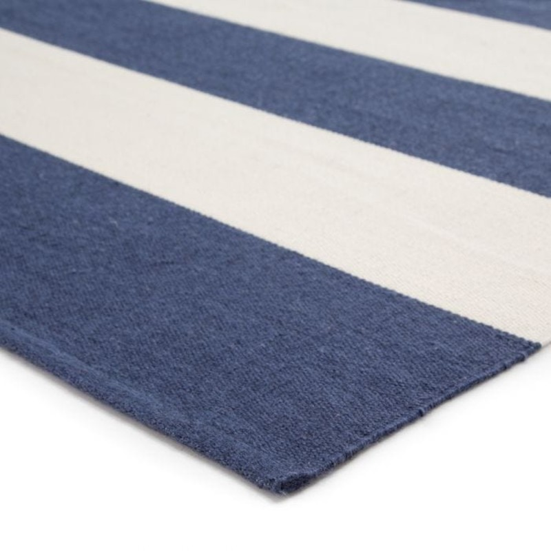 The bold stripe Remora area rug infuses both indoor and outdoor spaces with a classic colorway of deep blue and ivory. Hand woven of eco-friendly PET yarns; this durable rug is easy to clean and perfect for high-traffic areas. Free shipping  within continental US. Samples available for check out at Sandalwood Shoppes in Leland; NC.