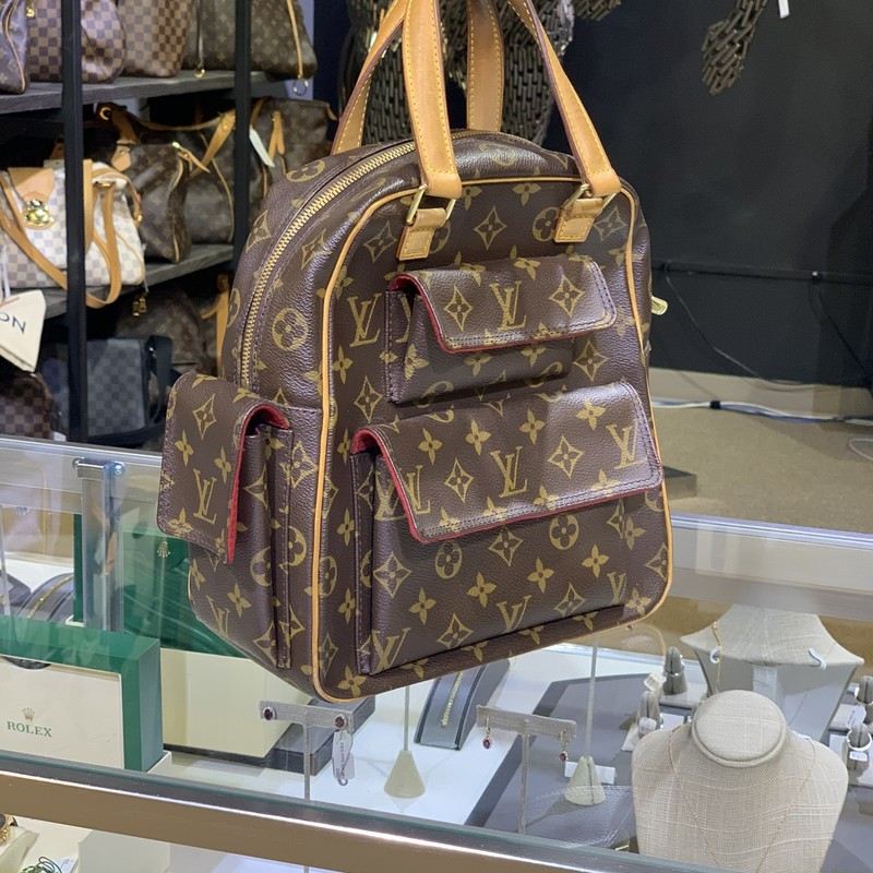 "LV Excentri-Cite Bag Mono, Mono, Size: IHH<br /> <br /> Stylish and practical, the Louis Vuitton Monogram Canvas Excentri-cite bag has a unique structure that will hold all your daily essentials. Inspired by classic utility bags, there are ample exterior pockets to hold your cell phone and other small items. You will love that this utilitarian-cool style is so luxurious at the same time.<br /> <br /> Overall Condition: Gently used<br /> Exterior Condition: Gently used<br /> Interior Condition: Gently used<br /> Designer: Louis Vuitton<br /> Material: Monogram coated canvas with leather trim<br /> Origin: France<br /> Authenticity Code: VI003<br /> Measurements: 10"" L x 5\"" W x 10.5\"" H<br /> Exterior Pockets: Two pockets with snap closure, one side flap pocket<br /> Interior Pockets: One flat pocket<br /> Handles: Double flat leather handles<br /> Handle Drop: 5\""<br /> Closure/Opening: Double zip closure<br /> Interior Lining: Red Alcantara lining<br /> Hardware: Goldtone"