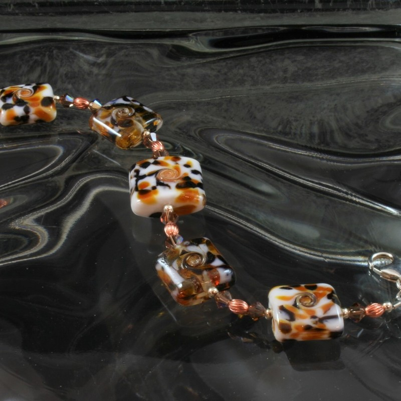 From the Serengetti collection of Gladmist Glass Design. Hand torched glass beads with sterling silver, Swarovski crystals and copper accents. Adjustable lobster clasp closure fits 7 1/2 or 8 inch wrist. Can be made to fit 8 1/2 inch wrist upon request.