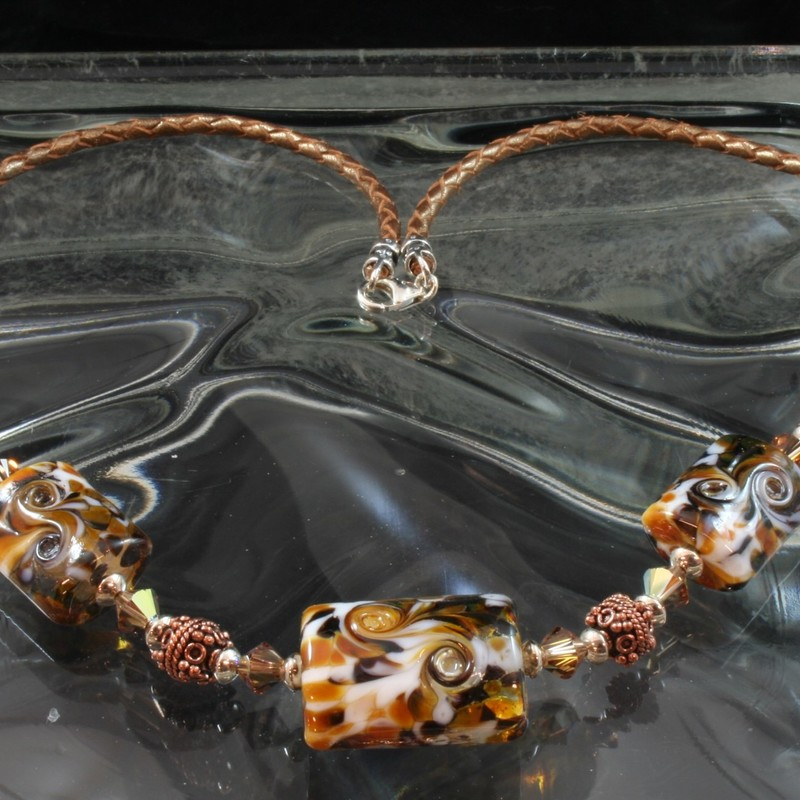 From the Serengetti collection of Gladmist Glass Design. Hand torched glass beads with sterling silver, Swarovski crystals and copper accents. Finished with Bronze colored braided leather and a lobster clap. Length is 20 inches.