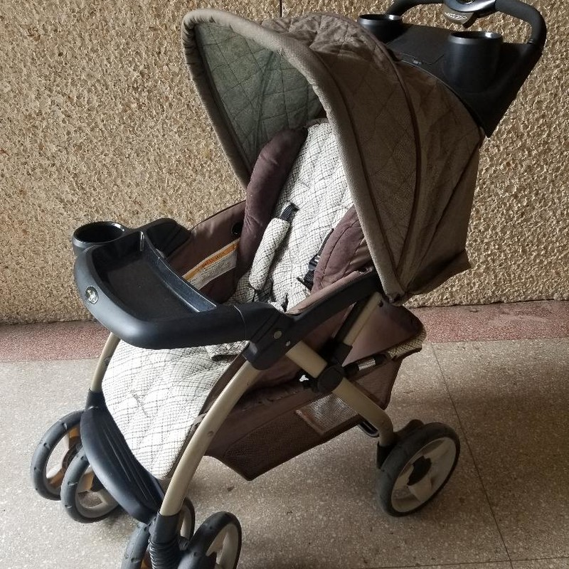 Eddie Bauer stroller<br /> Brown & plaid colors<br /> Large storage underneath<br /> Removable front tray<br /> Double drink holder<br /> Storage area with lid<br /> All straps & buckles intact<br /> Has some wear, priced accordingly<br /> More info can be found online<br /> * STORE PICKUP ONLY, NO SHIPPING.<br /> ** WE OFFER FULL CURBSIDE SERVICE.