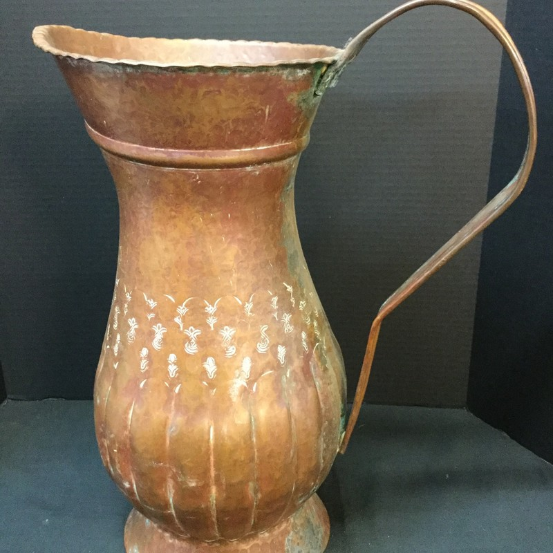 Large copper pitcher. Handmade in Egypt and etched around middle of body. Heavy and stands at 19 inches tall.