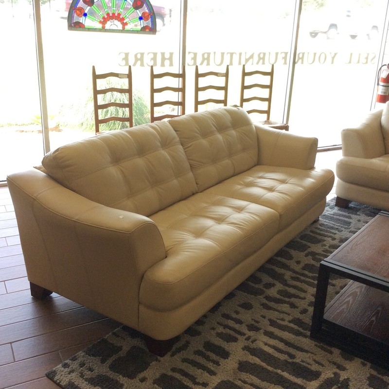This leather sofa is contemporary, comfortable and in perfect condition! Upholstered in a soft, smooth vanilla leather. All cushions are attached and tufted with ticking. Best of all, we have 2 of them!