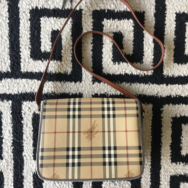 Gently used, vintage Burberry crossbody. Pebbled leather with classic Burberry plaid and smooth brown leather.Three compartments with interior zipper. Adjustable strap. Some worn spots, shown in photos.