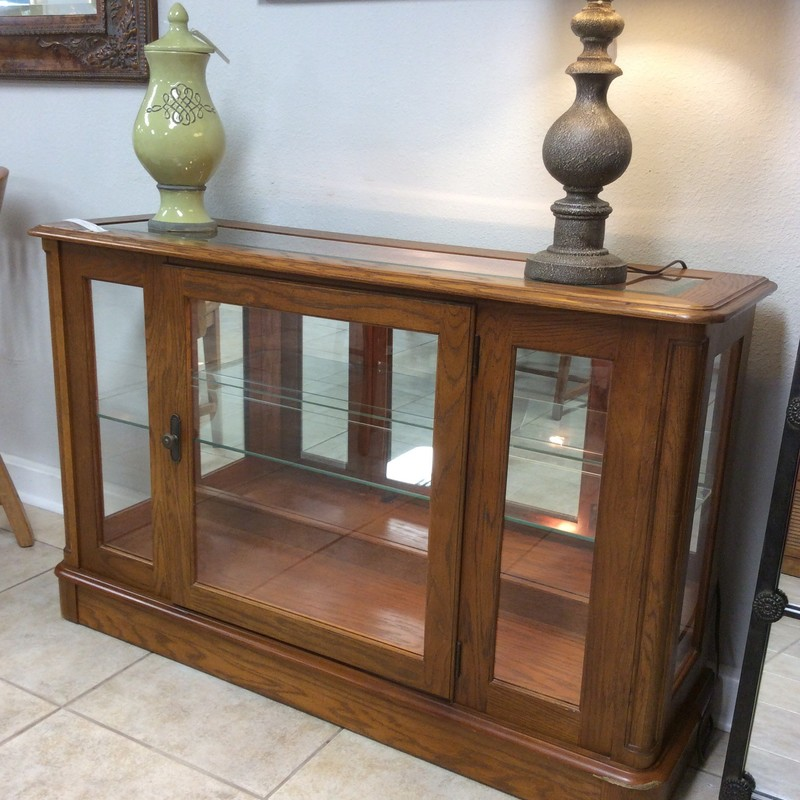 We have alot of bargains going on right now so you need to get in here - this is another one! This adorable curio console is a lovely combination of wood and glass. It features an oak wood finish, a glass inlay at the top, glass side panels, glass front door and a single glass shelf. All of that glass is sure to make your treasured items sparkle and shine!