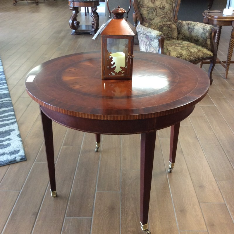 This handsome accent table by Baker Furniture is actually made in the U.S.A.!  It features a lovely dark cherrywood finish with a decorative inlay in the center. The tall, slim legs sit on tiny casters. It certainly has an Old World Charm to it!  It would make a great game table or sitting in a sunlit nook. Come by soon and take a look!