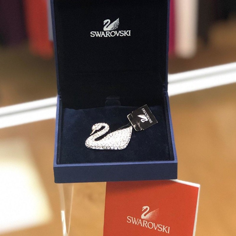 "The Swarovski Swan is brand new w/tag, box and certificate!<br /> Swarovski Swan Brooch Signed With Swan Logo, With Graduated Clear Sparkling Crystal Stones, Quality Silver Tone Jewelry Setting, Swan Logo Was Created In 1988, Elegant Swan Brooch By Swarovski, The Beak Is Gold Tone Color, The Eye Is Also Out Lined In Gold, Set With Graduated Clear Sparkling Crystals, Great Accessory Jewelry Piece, Vintage Swarovski Swan Brooch, Elegant Anniversary Gift, Gorgeous Birthday Present For Her, Beautiful Gift For Mom!<br /> <br /> Description:<br /> Swarovski Swan Brooch signed with the ""Swan Logo"" which was created in 1988.<br /> <br /> MEASUREMENTS:<br /> 2.1/4"" in diameter;<br /> 1.3/8"" in height;<br /> <br /> This elegant Swan brooch is set with graduated clear-sparkling crystal stones in a quality silver tone jewelry metal.<br /> The swan's beak is gold-tone and the eye is also out-lined in gold.<br /> The brooch has a functional ""C"" roll-over clasp.<br /> This gorgeous brooch is in excellent condition for its vintage age.<br /> It appears that it was never used or worn.<br /> <br /> NOTE:<br /> Swarovski's vision was to make ""a diamond for everyone"" by making crystals affordable.<br /> Swarovski and partners founded the company in 1895 and established a crystal-cutting factory in Wattens, Tyrol Austria.<br /> Swarovski entered the jewelry market in the United States in 1977."