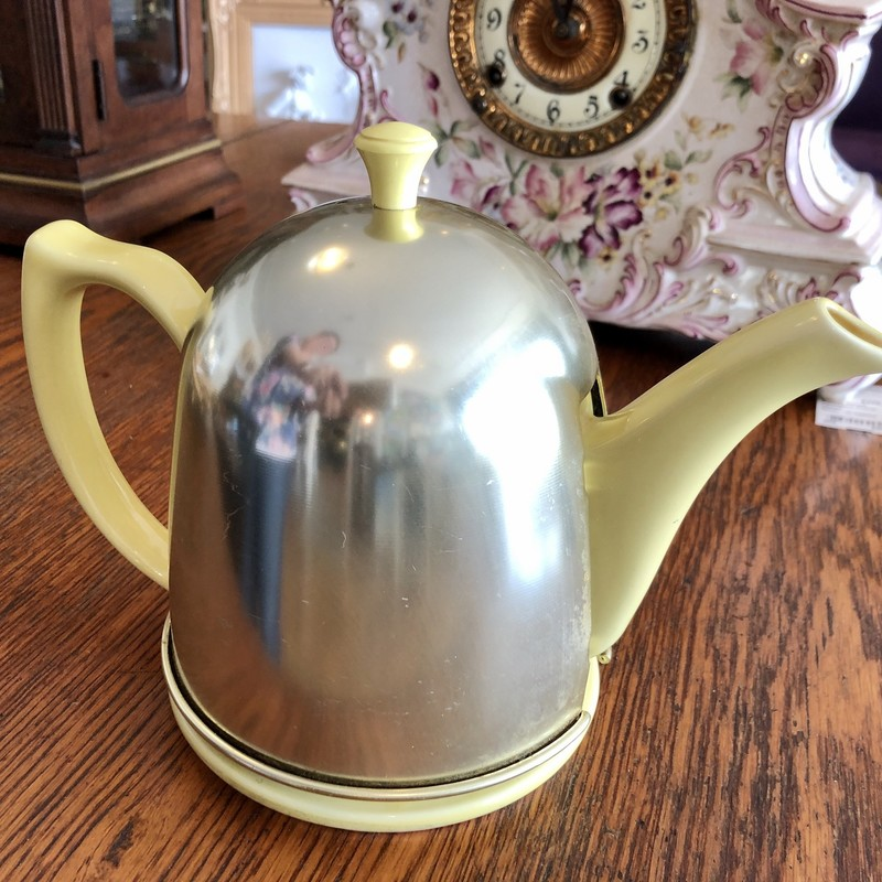 Vintage c. 1950s HALL China teapot in canary yellow.<br /> It has an aluminum cosy with felt lining so your last cup<br /> of tea is as hot as the first!  Teapot is heavy pottery with a built-in strainer at the base of the spout. It is marked on the bottom with the Hall trademark. Measures 7 1/8 inches high with the cover. Very nice design., Excellent condition, no chips, cracks, or repairs. The metal cover shows light surface wear.