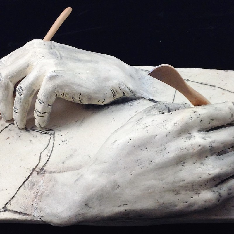 "Title: Drawing Hands, Artist: Fred Freeman, Medium: clay, Size: 8""H x 8"" W x 6""D<br /> Statement: This piece is a three dimensional representation of M.C Escher's ""Drawing Hand"", except the hands hold sculptural tools instead of pencils."