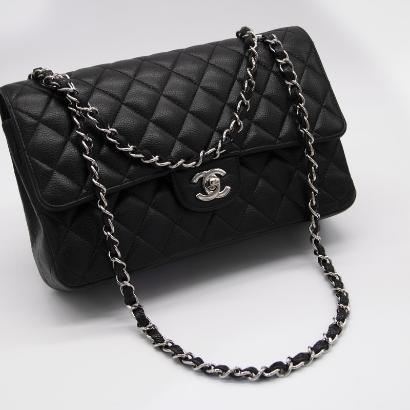 Chanel Medium Double Flap, Black, Size: CTHH<br /> <br /> Black quilted Caviar leather Chanel Classic Jumbo Double Flap bag with silver-tone hardware, convertible chain-link and leather shoulder straps, single exterior slip pocket at back, single zip pocket at flap underside, three interior compartments; dual with snap closure at flap, dual slip pockets at interior walls and CC turn-lock closure at front flap.<br /> <br /> Mint Condition