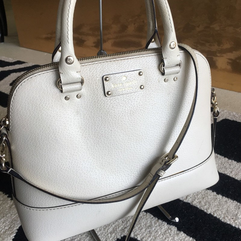 Used Kate Spade satchel bag. Nude leather with gold hardware. Removable/adjustable strap. Exterior has some markings and dirt build-up. Interior has small staining, but overall, gently used. Retail: $278.00