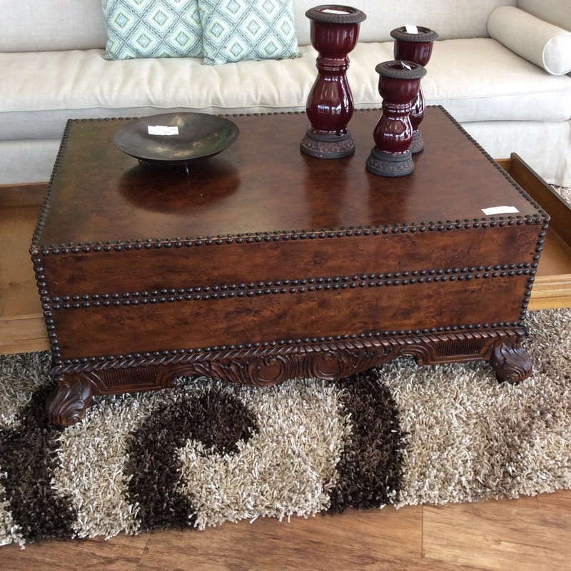 This chest-style coffee table is GORGEOUS! It features solid wood construction, and has burled walnut veneers covering the top and sides. There are 2 roomy drawers at the bottom of the outter sides, as well. There are more than 800 nailhead accents, and a handsome carved base. There is also a matching drum table that is available for purchase seperately.