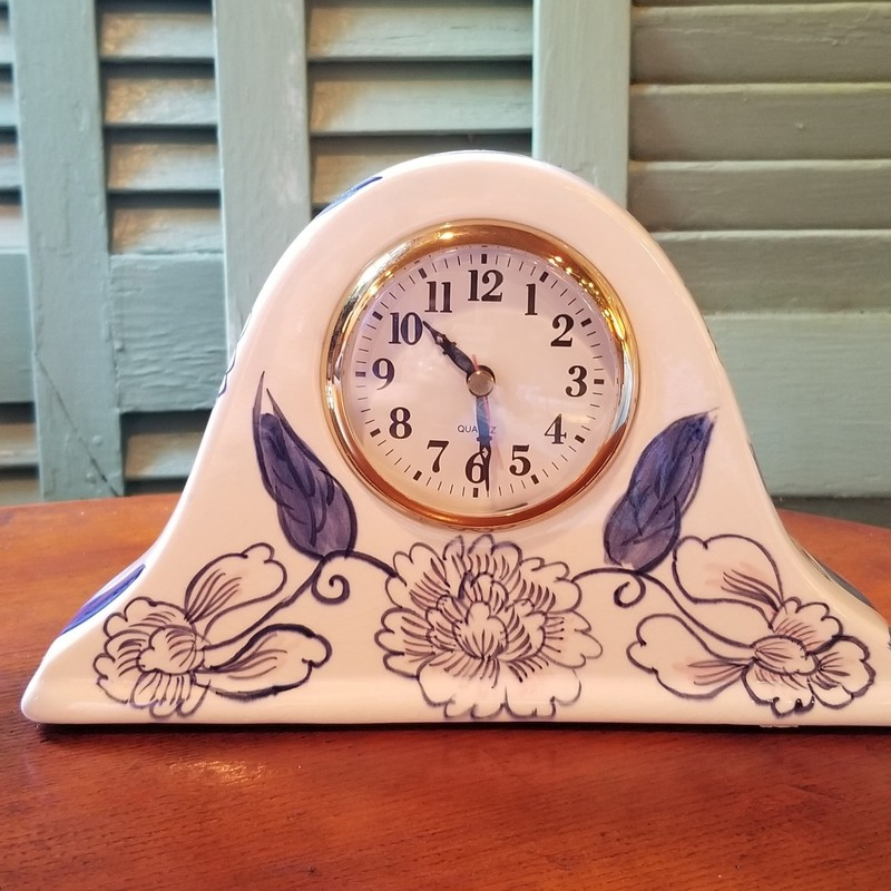 "CERAMIC CLOCK<br /> This pretty floral clock in blue and soft pink has a pop out center that holds a AA battery.<br /> 10"" wide at base<br /> 6"" high"