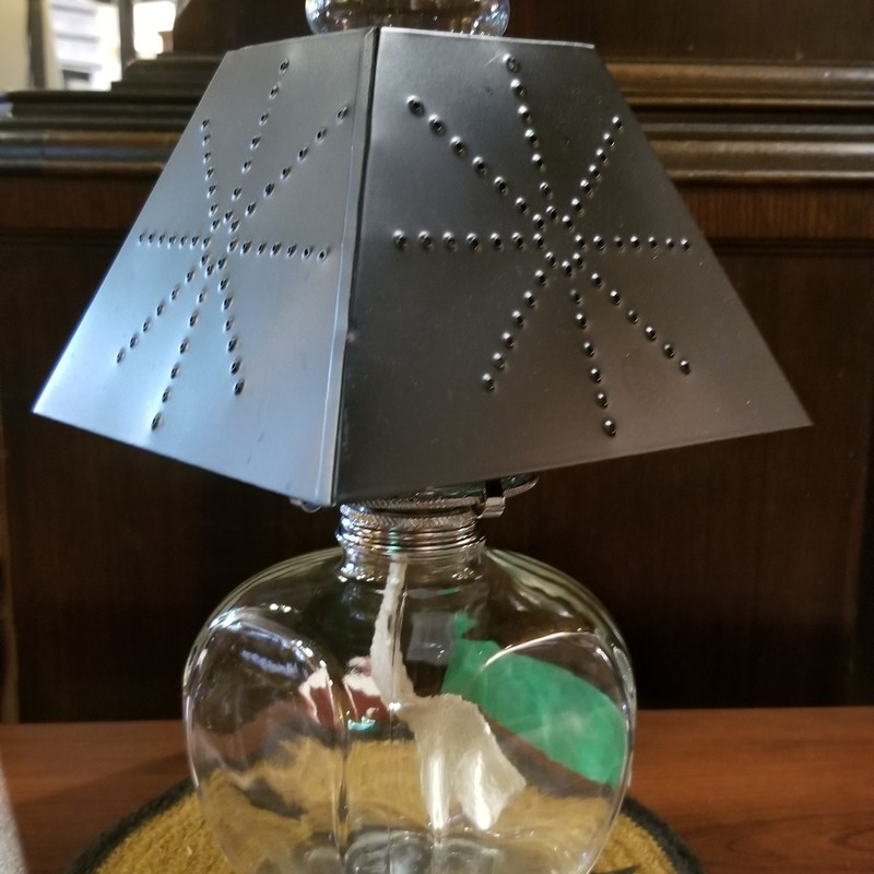 "GLASS OIL LAMP<br /> Clear glass lamp with punched tin shade. Lovely for a bedroom, kitchen or porch lamp.<br /> Shade is 7"" wide<br /> Lamp is 14"" tall"