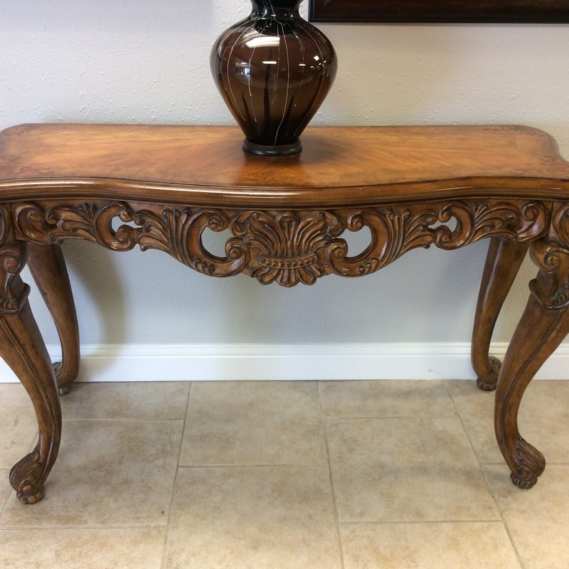 This sofa table would be a lovely addition as well as adding a little drama to your room! Heavily and ornately carved, it features a dark wood finish with a delicate scrollwork inlay in the corners and sits atop 4 beautifully carved claw feet. Forget simple, clean lines - this sofa table has a statement to make!