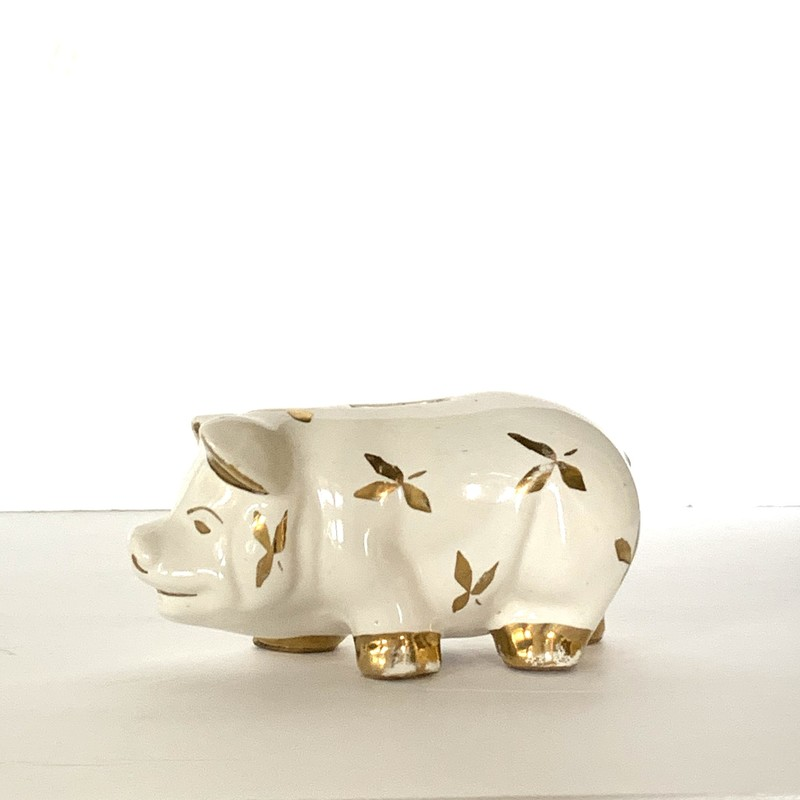 This pig got close enough to King Midas to take on some gold, but stayed far enough away to keep its soothing china finish! Now it is a cute piggy bank.