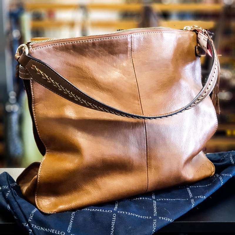 Beautiful Tignanello Purse.<br /> - Brown leather exterior<br /> - Gold-tone hardware<br /> - Zip-top closure<br /> - Shoulder straps/handle with 10 in. drop<br /> - Footed bottom<br /> - Interior features: two slip pockets, one zip pocket, four card slots, keyclip and two penloops<br /> - Dust bag included<br /> - W: 14 in. H: 12 in. D: 4.5 in.<br /> <br /> * Please note that these measurements and pictures are for reference only and may vary slightly from the original.