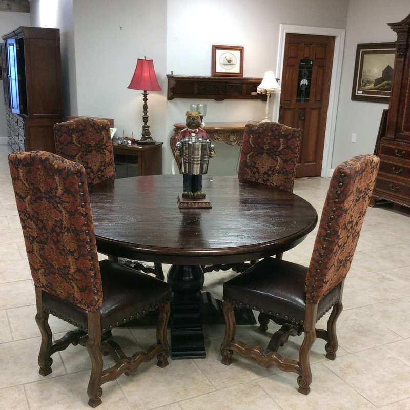 This dining set is from LAURIE'S in Tomball.The pedestal table is made of solid, rough hewn wood and has an espresso finish. The 4 chair seats are  upholstered in a dark chocolate leather, and the chair backs have a vibrant orange/red/gold/brown floral upholstery. The solid wood chair frames are beautifully carved, and there are lots of medium-sized nailhead accents on each chair.