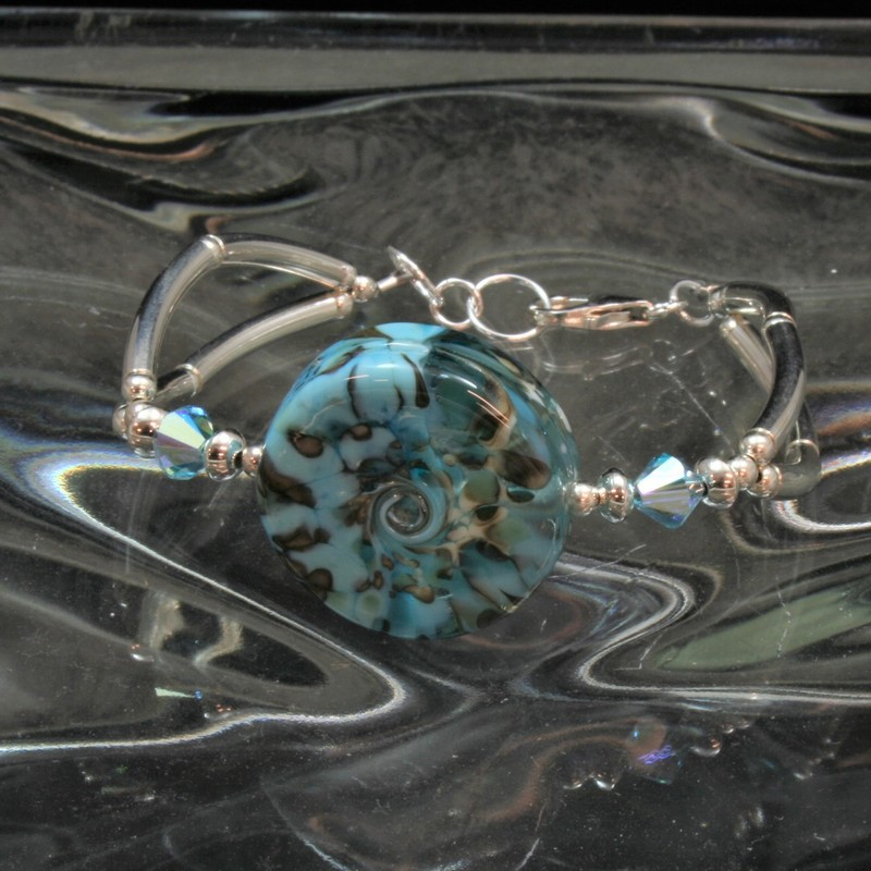 "From the ""Seaside Cliffs\"" collection of Gladmist Glass Design. Hand torched Lampwork glass beads combined with Swarovski crystals and Sterling Silver. Adjustable lobster clasp closure fits wrists 7 1/2 to 8 inches. Can be made to fit a larger wrist upon request."