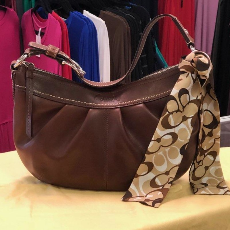 "COACH, Brown, W/COACH Scarf<br /> Fabulous mid-sized version of the pleated ""SOHO"" hobo bag!<br /> Made from pleated brown leather, with silver hardware.<br /> - Wide leather strap with buckle drops 8-9""<br /> - Large lozenge signature hang tag<br /> - Back zippered pocket<br /> - Zip top closure<br /> - Brown grosgrain lining<br /> - Inside zip pocket<br /> - Two slip pockets<br /> - Serial no. G0973-F13730<br /> - The Consignor is selling the COACH SCARF with the Bag.<br /> CONDITION:<br /> The leather is in excellent condition, overall the bag could pass for new!"