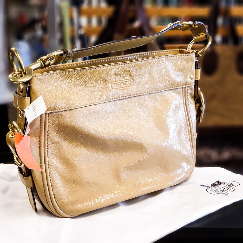 Beautiful Coach 12735 Purse.<br /> - Brand new<br /> - Tan patent leather exterior<br /> - Silver-tone hardware<br /> - Zip-top closure<br /> - One handle<br /> - Interior features: two slip pockets and one zip pocket<br /> - Dust bag included<br /> - W: 13.5 in. H: 10 in. D: 4 in.<br /> <br /> * Please note that these measurements and pictures are for reference only and may vary slightly from the original.