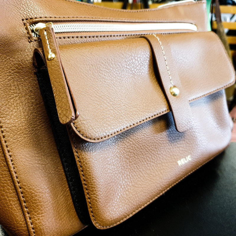Beautiful Relic Purse.<br /> - Brand new<br /> - Brown and black faux leather exterior<br /> - Gold-tone hardware<br /> - Zip-top closure<br /> - Front zip closure pocket and magnetic button closure pocket<br /> - Adjustable shoulder straps with 27 in. drop<br /> - Interior features: polka dot lining, two slip pockets and one zip pocket<br /> - W: 12 in. H: 8.5 in. D: 2.75 in.<br /> <br /> * Please note that these measurements and pictures are for reference only and may vary slightly from the original.