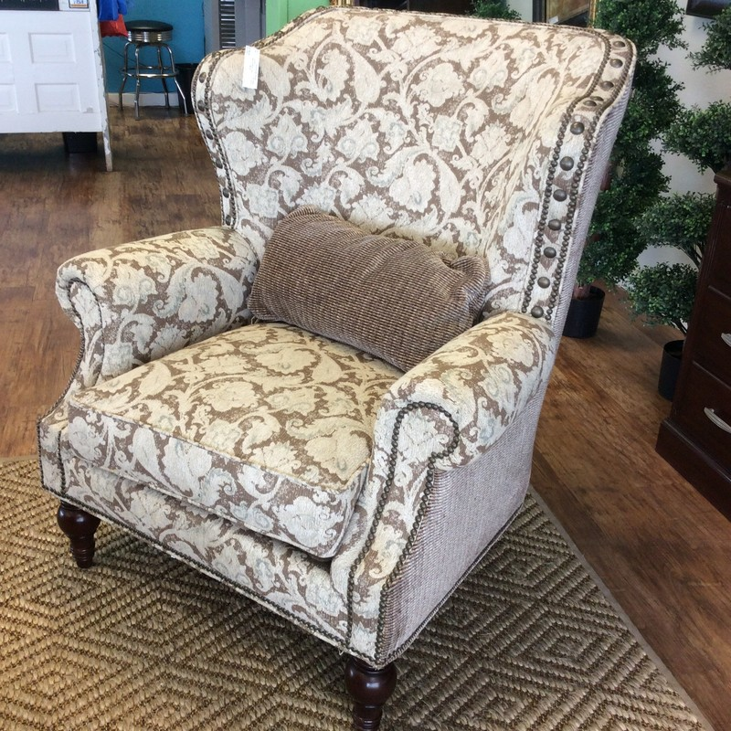 This wingback by Sherrill is lovely!  Larger than most wingbacks, it kind of wraps itself around you in style and luxury. Upholstered in an attractive brown and cream pattern of florals and scrollwork that is soft and soothing to the eyes. The sides and the back are upholstered in a striped pattern of the same colors. A nailhead trim pulls it all together. It's very comfortable and in good condition.
