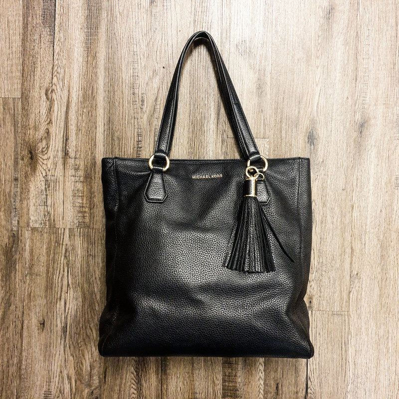 Beauiful Micheal Kors Purse.<br /> - Black leather<br /> - Zip-top closure<br /> - Removable tassel<br /> - Two handles with 9.5 in. drop<br /> - Interior features: two compartments, four slip pockets and one zip pocket<br /> - W: 15 in. H: 13.5 in. D: 4.5 in.<br /> <br /> * Please note that these measurements and pictures are for reference only and may vary slightly from the original.