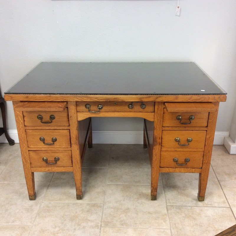This is a charming older desk! Solid wood construction, it features several drawers with dovetail jointing, a file cabinet drawer, 2 pull-out trays and a burgundy leather top bordered by a nailhead trim. A nice thick glass top finishes it off with vintagy brushed hardware.