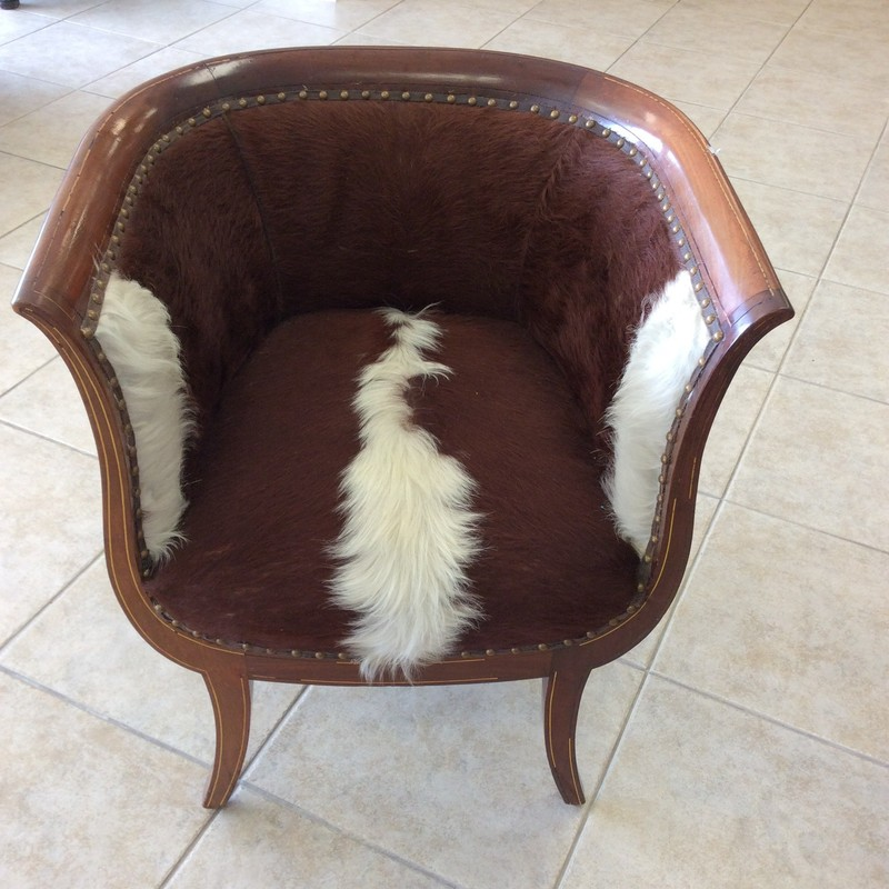 If rustic, western, or Texan is your thing this small barrel chair would be an attractive addition. The outside has been upholstered in leather with a nailead trim.