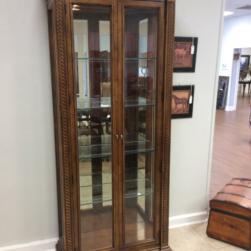 This display/curio cabinet by HENREDON is in excellent condition! It features solid OAK construction and has a medium-dark, stained finish. The carved details down both sides of the front are exquisite. Inside, there are 4 adjustable glass shelves each with plate grooves, as well as 2 dimmable lights. ONLY $795!
