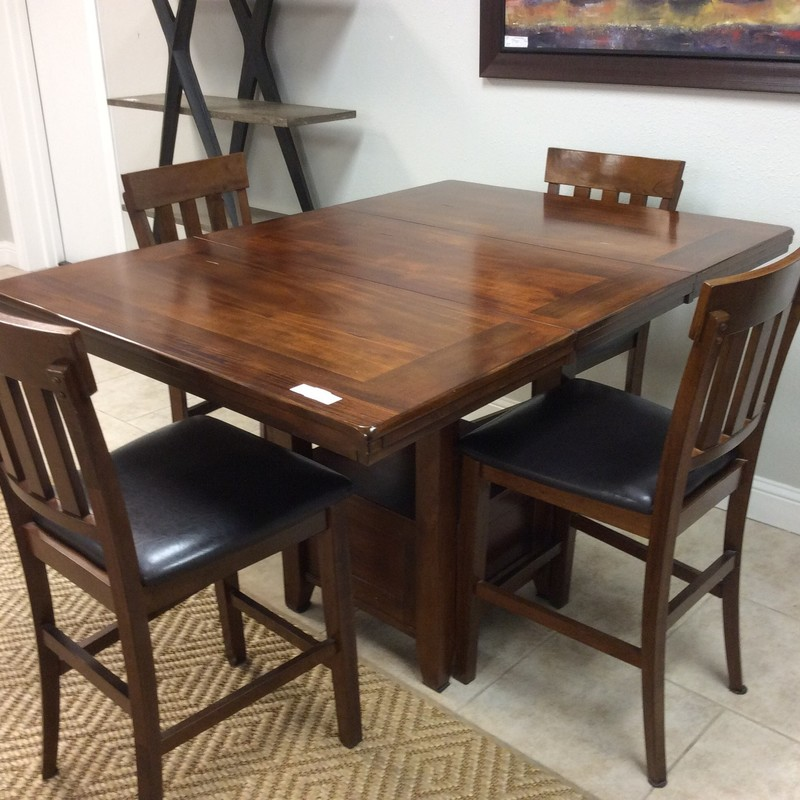 "This handsome dinette set is from ASHLEY Furniture, and it is in fabulous condition. The 42"" square table is solid wood and has a pretty cherry finish. When the 18"" leaf is inserted, the table becomes a 60""x42"" rectangle. The table also has a lower shelf underneath. The 4 chairs are also solid wood and have black leather-like upholstered seats. ONLY $595!"