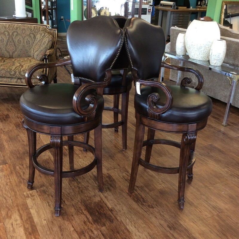BARGAIN ALERT!!! This trio of BERNHARDT bar chairs is in extraordinary condition, and priced well at only $595 for the set. They feature solid wood construction with handsome carved details and a dark walnut finish. They are upholstered in a rich, soft chocolate colored leather and there are hundreds of nailhead accents on each chair. Best of all, though, is that they SWIVEL!