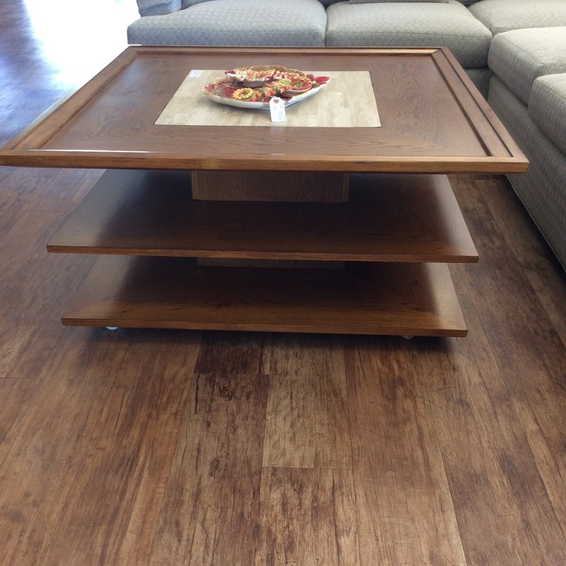 This unusual coffee table is solid oak with a pretty stained golden finish. There are 3 tiers altogether, and the lower 2 can be used for books or to display items. The center top has a handsome travertine insert, as well. ONLY $395!
