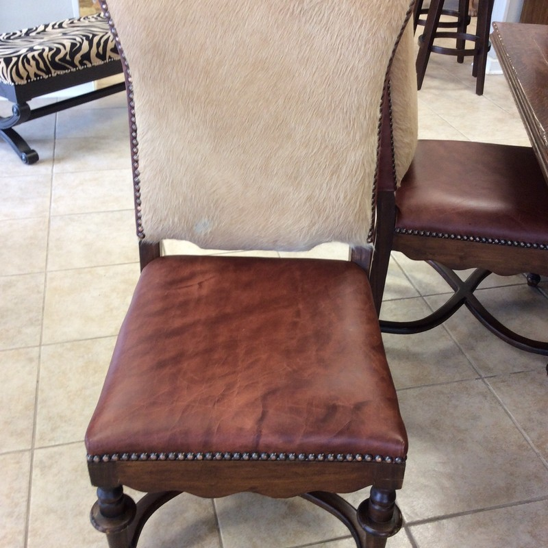 This GORGEOUS set of chairs was originally purchased at THE ARRANGEMENT for almost $500 per chair. You now have a chance to own FOUR of them for only $895! They are solid wood with a walnut finish and handsome carved details. The seats and chair backs are covered in high grade cow leather. The fronts of the seat backs are covered in genuine cow fur. Each chairs has hundreds of nailhead accents, too.