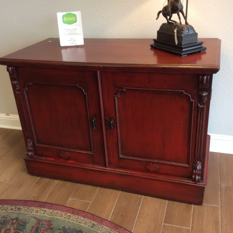 This is a great piece! This spacious cabinet has solid wood construction and has been painted a rich, rusty red. Large cabinet doors reveal an interior that is perfect for storage or it could be used for media. Looks like an older piece, character and charm!