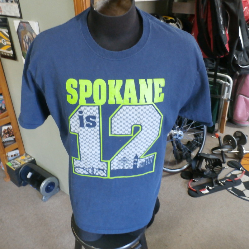 Seattle Seahawks &quot;Spokane Is 12&quot; shirt blue size XL 100% cotton #23868<br /> Rating: (see below) 3-Good Condition<br /> Team: Seattle Seahawks<br /> Player: 12th Man<br /> Brand: Port &amp; Co.<br /> Size: Men&#039;s XLarge  (Measured: 24&quot; Wide, length 29&quot;)<br /> Measured: Armpit to armpit; shoulder to hem<br /> Color: blue<br /> Style: short sleeve; screen printed<br /> Material: 100% cotton<br /> Condition: 3- Good Condition; wrinkled; some pilling and fuzz; material is stretched and worn from wearing and washing; some discoloration and fading; no rips or tears; 2 small, light white marks on front above the &quot;O&quot;  (see photos)<br /> Item #: 23868<br /> Shipping: FREE