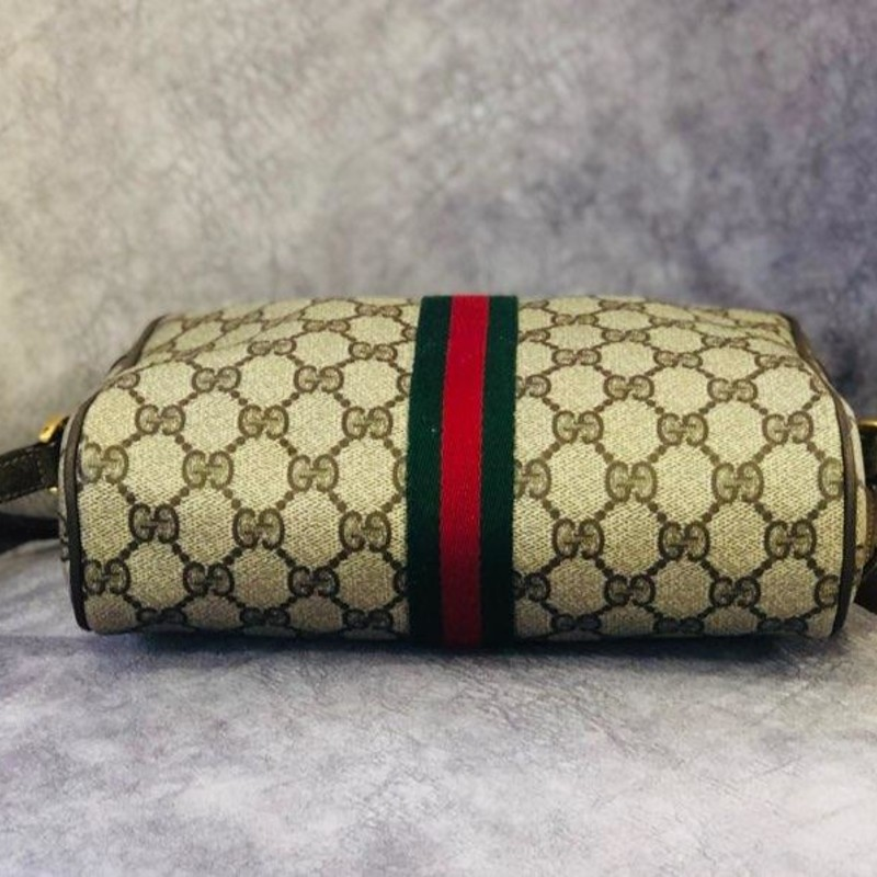 "GUCCI (Authentic), Vintage<br /> Vintage Khaki Monogram Leather Camera Brown Canvas Shoulder Bag<br /> 8.5""L x 2.5""W x 6.5""H<br /> Authentic Vintage Gucci ""Accessory Collection"" Web Khaki Monogram Camera Shoulder Bag.<br /> - Dimension: appr. 8.5""L x 2.5""D x 6.5""H.<br /> - Adjustable shoulder strap, up to 19.5"" drop.<br /> - Material: coated canvas. Leather strap and trim.<br /> - Top zip closure. Golden tone hardware/scratched. Front zip pocket.<br /> - Inner tag Gucci Accessory Collection Made in Italy/letters are faded. Serial # 111.02.004. Comes with Gucci Accessory Collection dust bag.<br /> The bag is clean, no odor, no tears, has light leather scuffs.<br /> Est. Retail Price: $750.00"
