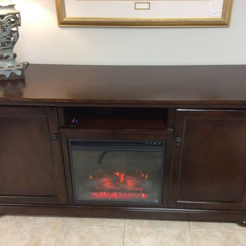 This handsome ASHLEY cabinet has a fireplace insert in the lower center. The fireplace functionality is controlled by a wireless remote. The cabinet itself appears to be solid wood, and is set up for media. There is a single adjustable shelf behind each of the side doors. ONLY $745!!!