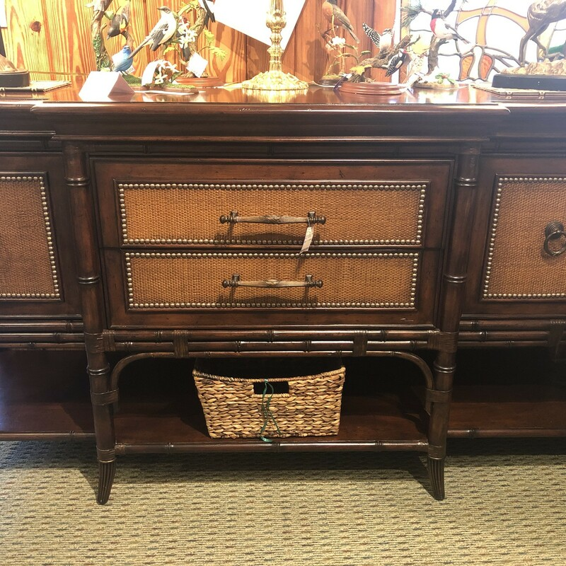 Tommy Bahama Sideboard, Used, Size: 38t 22d 72w<br /> <br /> High-quality Tommy Bahama Sideboard in rich tobacco brown.  Original price $2,800.  This gorgeous piece has nailhead trim with burnished maple and dark cherry inlay top, and rosewood woven door panes, plus removable felt lined divider in drawer for silverware.<br /> Please note this piece has minor damage along bottom shelf in rear of sideboard.  It isn't noticable unless pointed out.