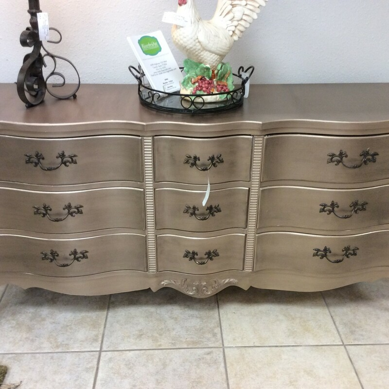 "It's been a rough year, you deserve a little ""glam"" and this dresser will fit the bill! The traditional and classic lines will remind you of a simpler time. But this one has been given a new chic lease on life. Painted a metallic champagne with the loveliest of sheens, it features 8 drawers with dovetail jointing and vintagy hardware. Beautiful feminine, curvy lines define this piece. Turn your bedroom into a ""boudoir"", you deserve it!"