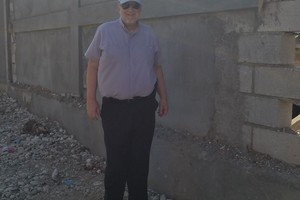 Fr Frank in front of the wall around the Norwich Outreach Center .
