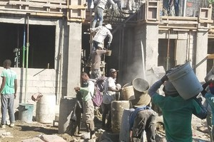 Workers mixing concrete and taking it up to the second floor.